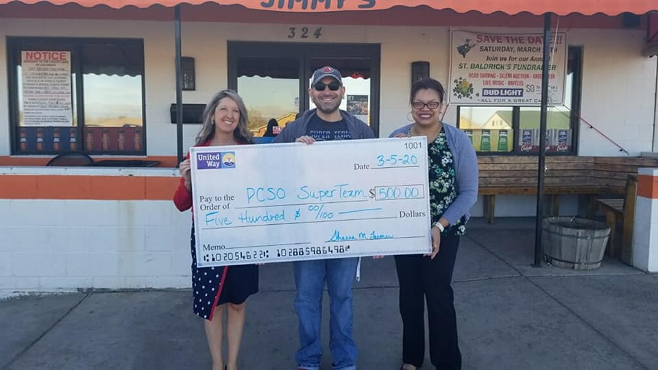Shanna M. Farmer, CEO of United Way of Pueblo County and Director of Marketing, Bianca Hicks present Superteam PSCO Captain Brad Riccillo a check for $500 at Jimmy's Tavern.