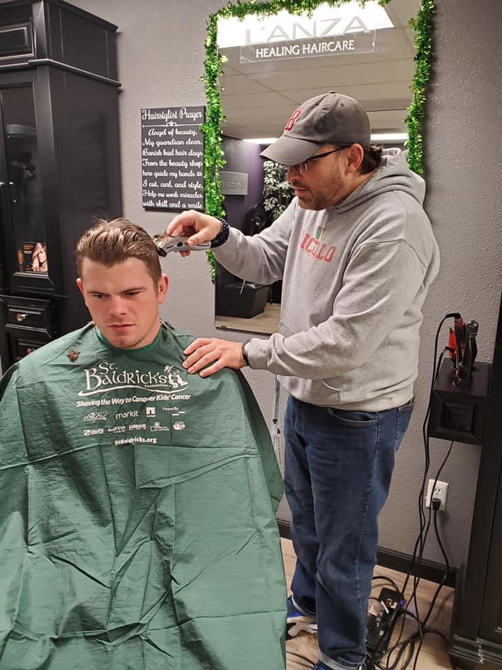 Superteam PCSO Capitán Brad Riccillo afeita la cabeza del sargento Kerrick Meinecke en el Aura Salon