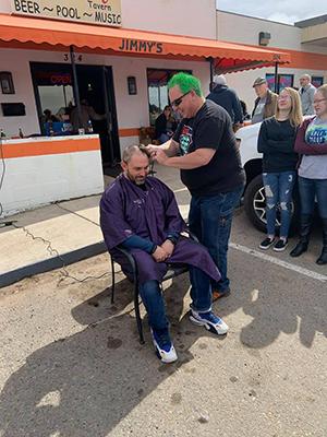Grant Shay, coordinador del evento anual St. Baldrick's en Pueblo West, afeita la cabeza del capitán de Superteam PCSO Brad Riccillo en Jimmy's Tavern