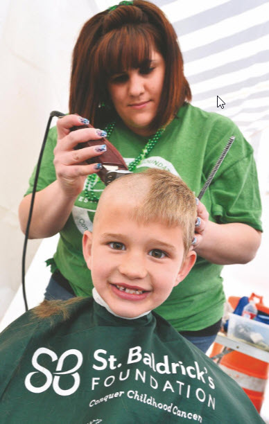 Sawyer Rocchio smiles as he gets his hair cut by Jamie Owens, owner of Jalyn Styles, during the previous St. Baldrick's Foundation's haircutting event at Jimmy's Tavern in Pueblo West to help battle childhood cancer. [FILE PHOTO]